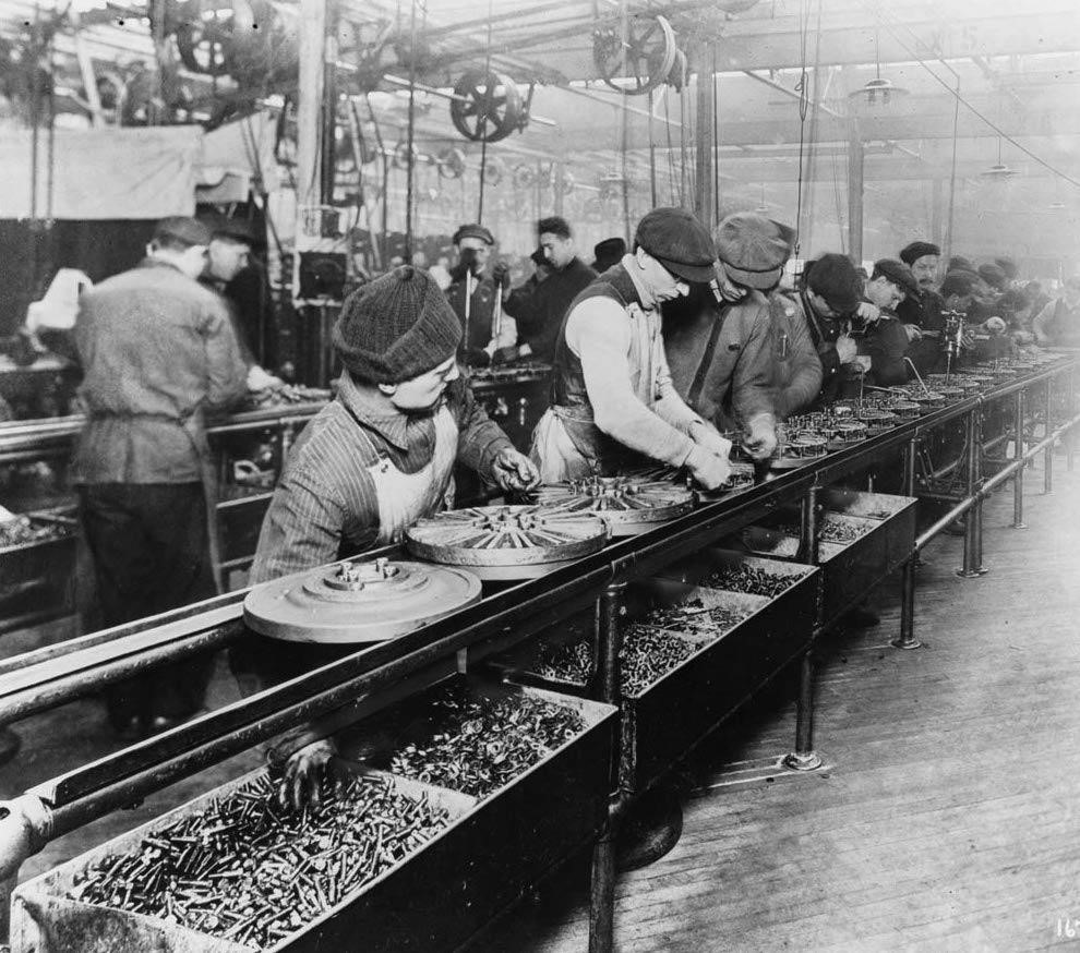 Ford Motor Co. workers on the first moving assembly line in 1913 assembling automobile magnetos and flywheels