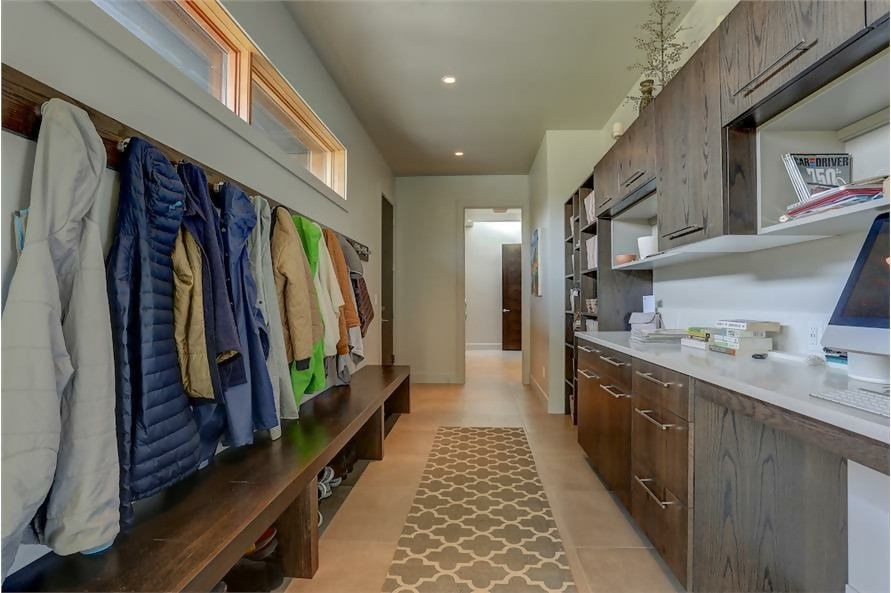 Mudroom with a wall of hooks for jackets and sweaters and a bench with shoe storage