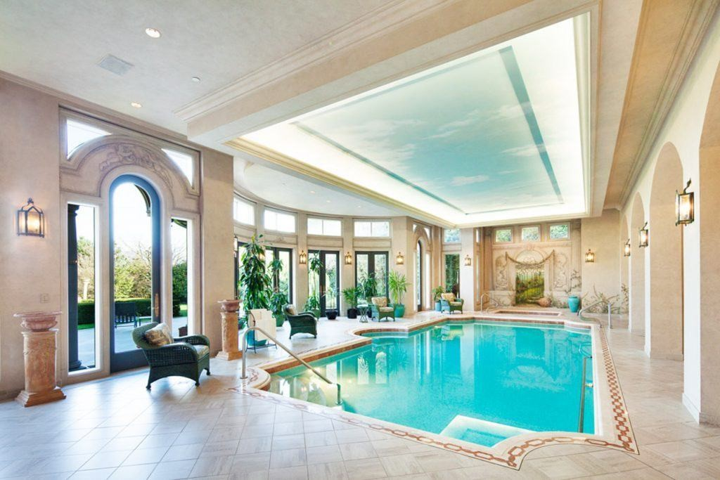 Indoor pool framed by large glass windows and wide arches