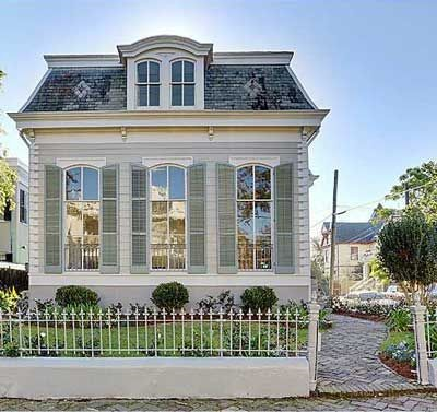 Colonial style home with window shutters and a mansard roof