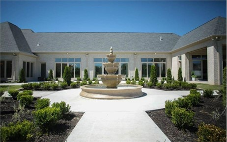 Large water fountain in a courtyard, focal point of backyard of U-shape European home