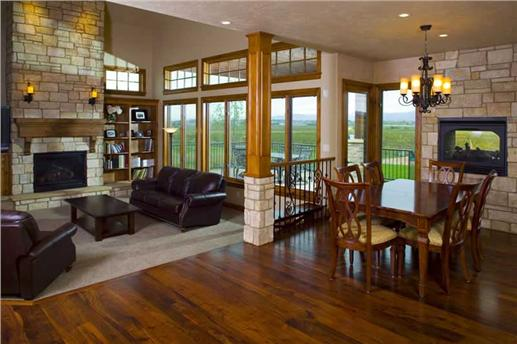 Open floor plan with family and dining areas separated by column with railing