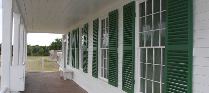 Porch on white house with green louver window shutters