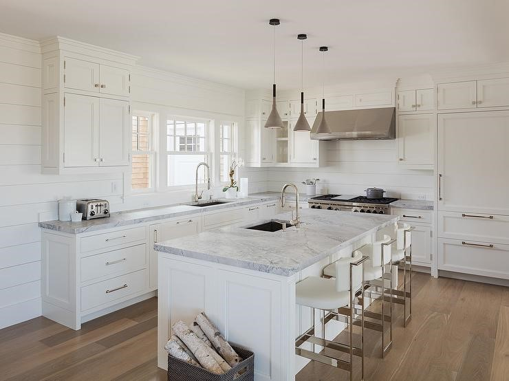 All-white L-shape kitchen with stainless steel accents