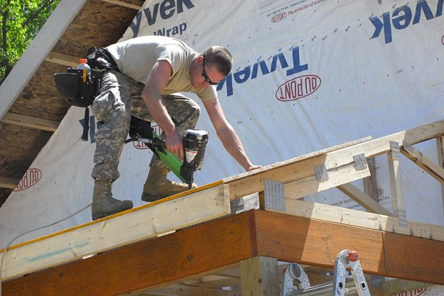Framing carpenter attaching sheathing to porch roof