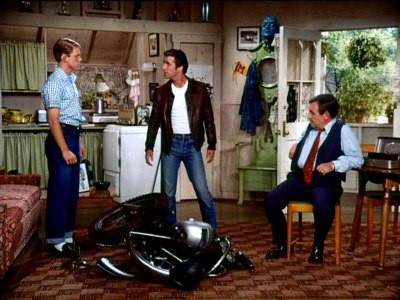 Scene from Happy Days with Richie Cunningham, Fonzie, and Richie's dad in Fonzie's garage apartment
