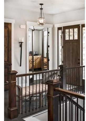 Entry hall with stairs that have wood-and-metal railings going downstairs