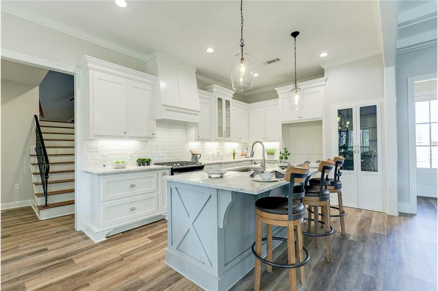 Open-plan kitchen with blue island and walk-in pantry
