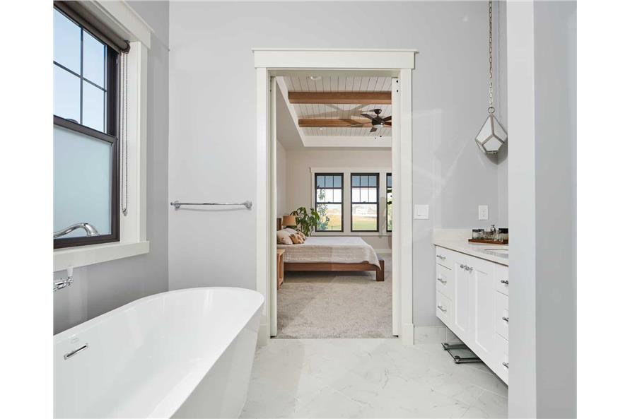 White bathroom with floating vanity and free-standing tub