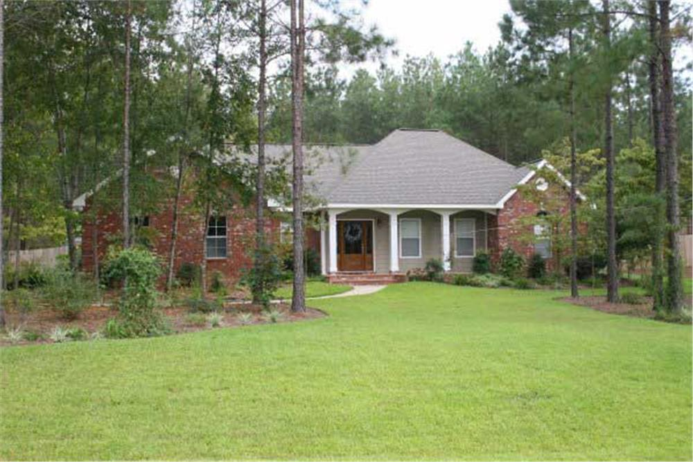 1-story Country home on wooded land with a large clearing in front