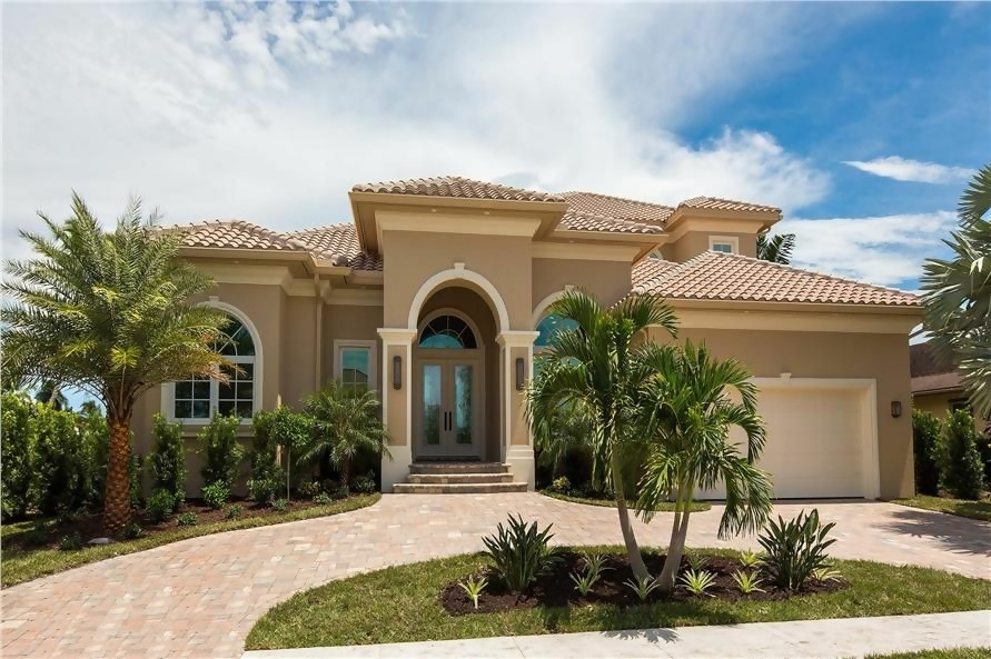 Majectic Mediterranean style coastal home with tan stucco siding, white trim, and tile roof