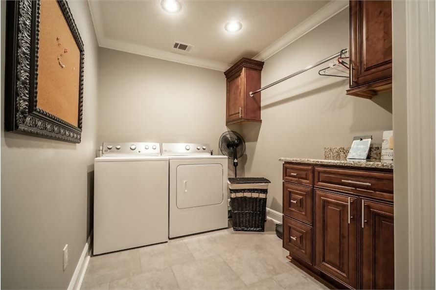 Compact, organized laundry room with cabinets, clothes rod, and countertop