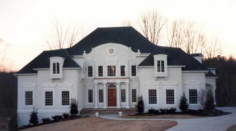 2-story Colonial-style home with white columns that frame the front doo