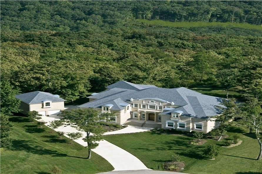 Aerial shot focuses on the massive lush grounds and natural landscape around house plan #106-1189
