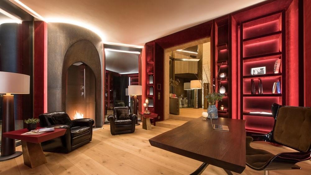 Secret home office hidden behind walls of red velvet library