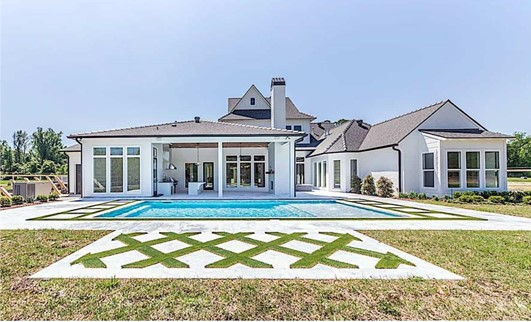 Colonial style home with large pool and patio in the backyard