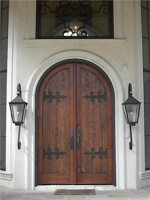 Arched double wooden doors with large, elaborate iron hinges