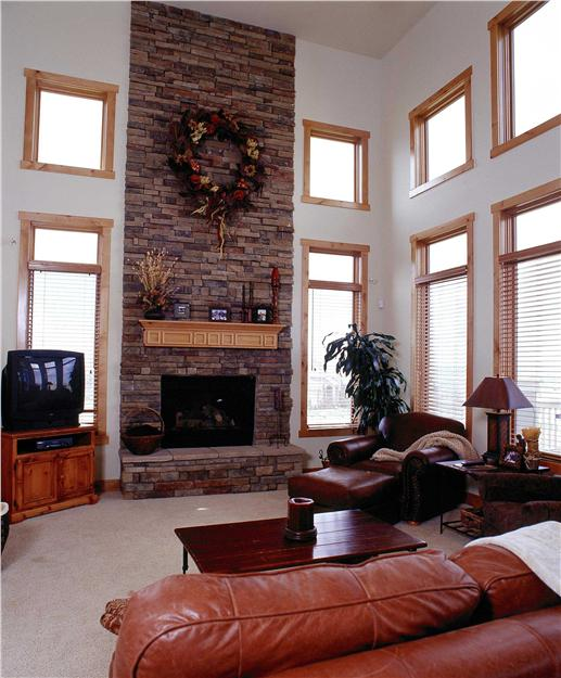 Windows, windows and more windows in the double-story great room with stone fireplace