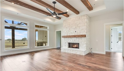 Great Room with high timber-accented ceiling and white walls and fireplace