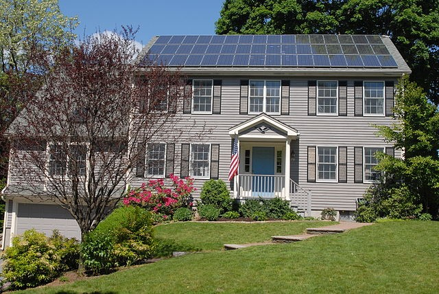 Colonial style home with an array of solar panels on the roof