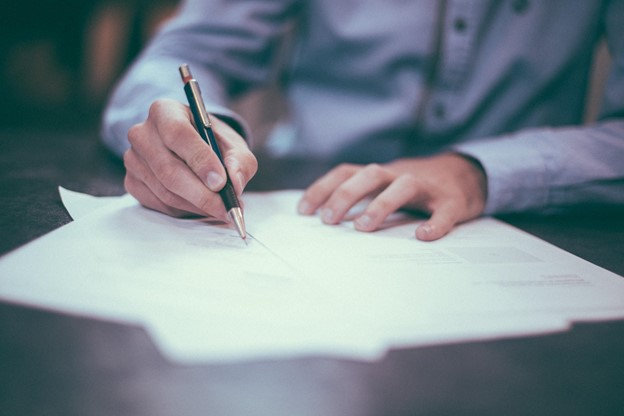 Man in blue shirt at a desk signing papers using a pen