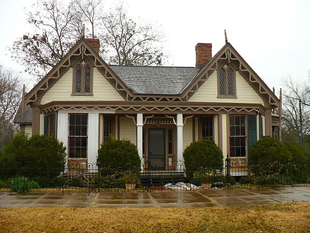 Beige and brown home with pointed wind ws and scrollwork along double gables