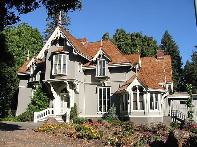 Beige and white home built in Carpenter Gothic style with oriel windows