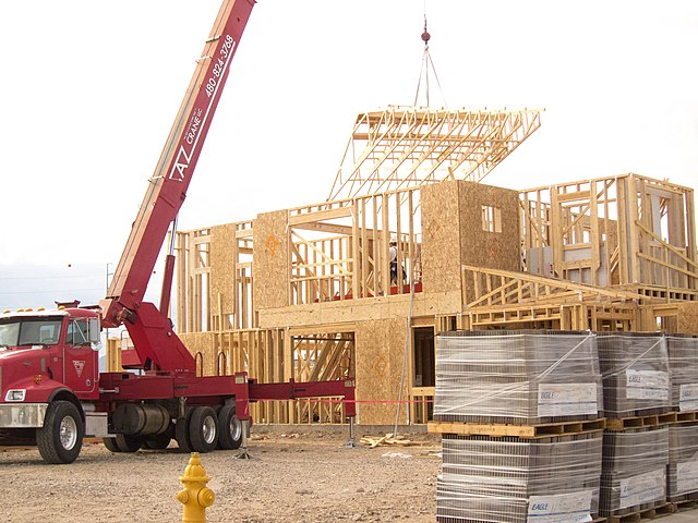 Articulated truck-bed-mounted crane at a job site placing a roof truss in place on a house