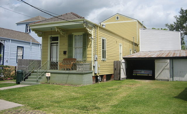 Camelback style shotgun house with yellow siding