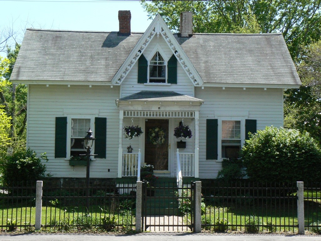 White Gothic Revival house with gingerbread trim and steep gable rood