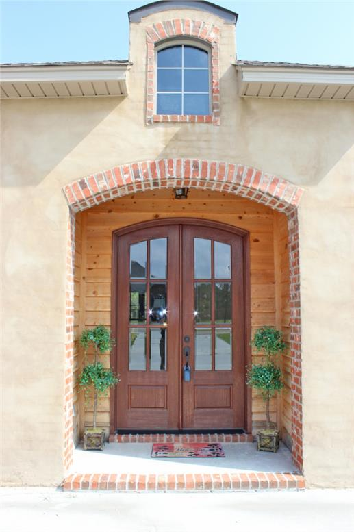 Double arched wooden doors on Acadian style home with stucco siding