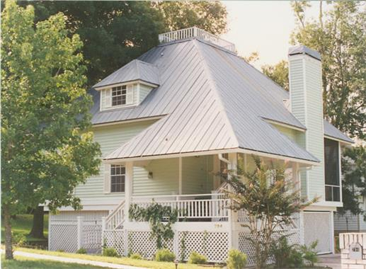 "Steeply sloped hip roof with metal roofing and ""lookout"" deck at top"