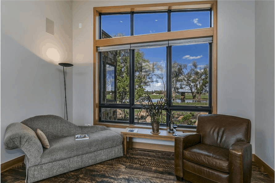 Curvy sofa, leather recliner, and large window in Contemporary style home