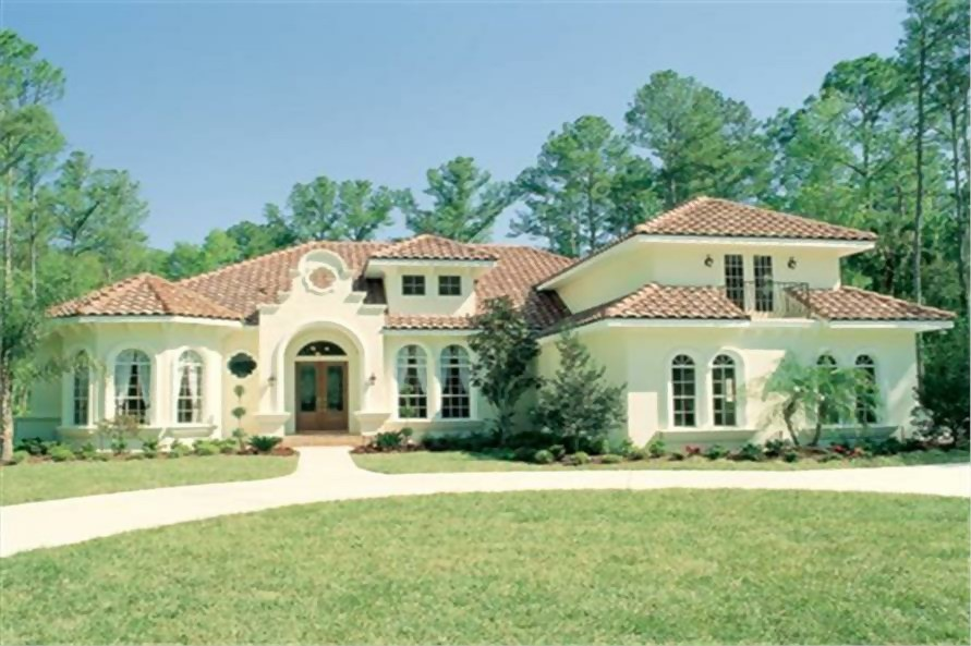 Spanish style home with beige stucco, scalloped parapet, and red-tile hip roof