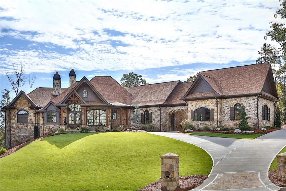 European Country Estate style home with porte cochere between its 1- and 2-car garages
