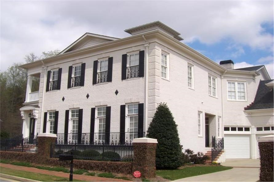 White Federal style home with large main-floor windows and front door off to the left side