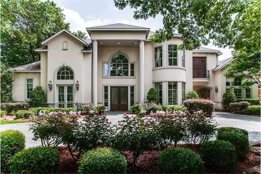 Luxury home with balanced number of tall, narrow windows on both floors of turret and 2-story-high entry porch roof