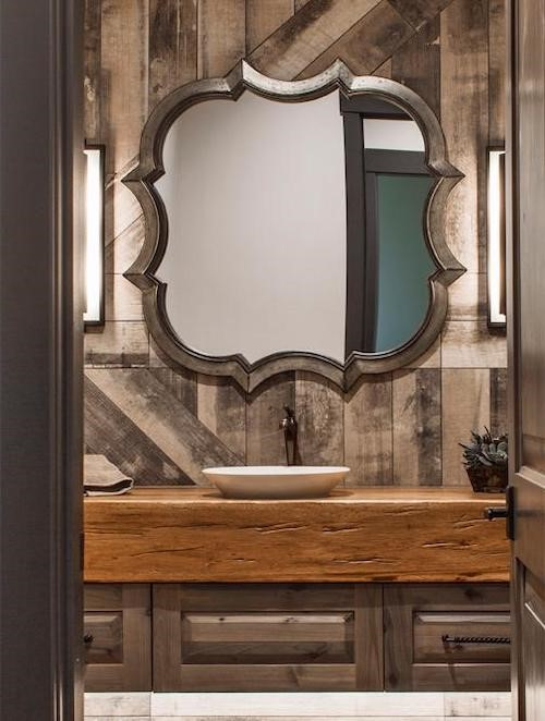 Wood-themed bathroom with unusually shaped mirror