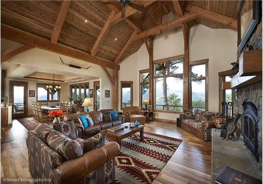 Great Room with vaulted wooden exposed-beam ceiling in a log home