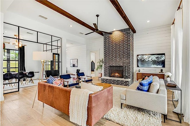 Exposed ceiling beams stained dark brown flanking a fireplace chimney in a stylish Great Room