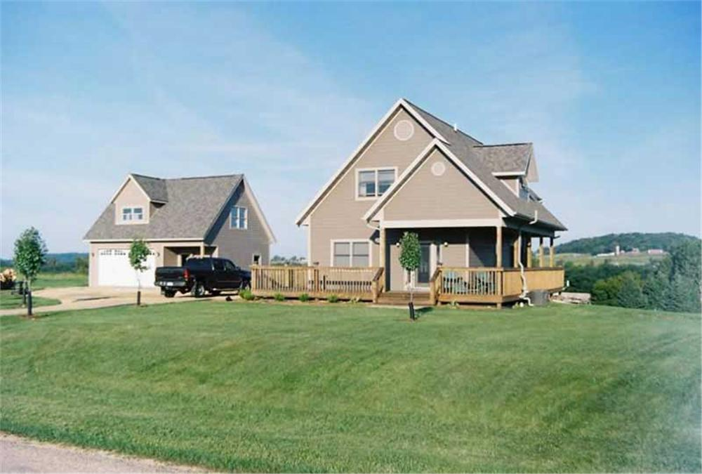 Farmhouse style home with detached garage off to the left