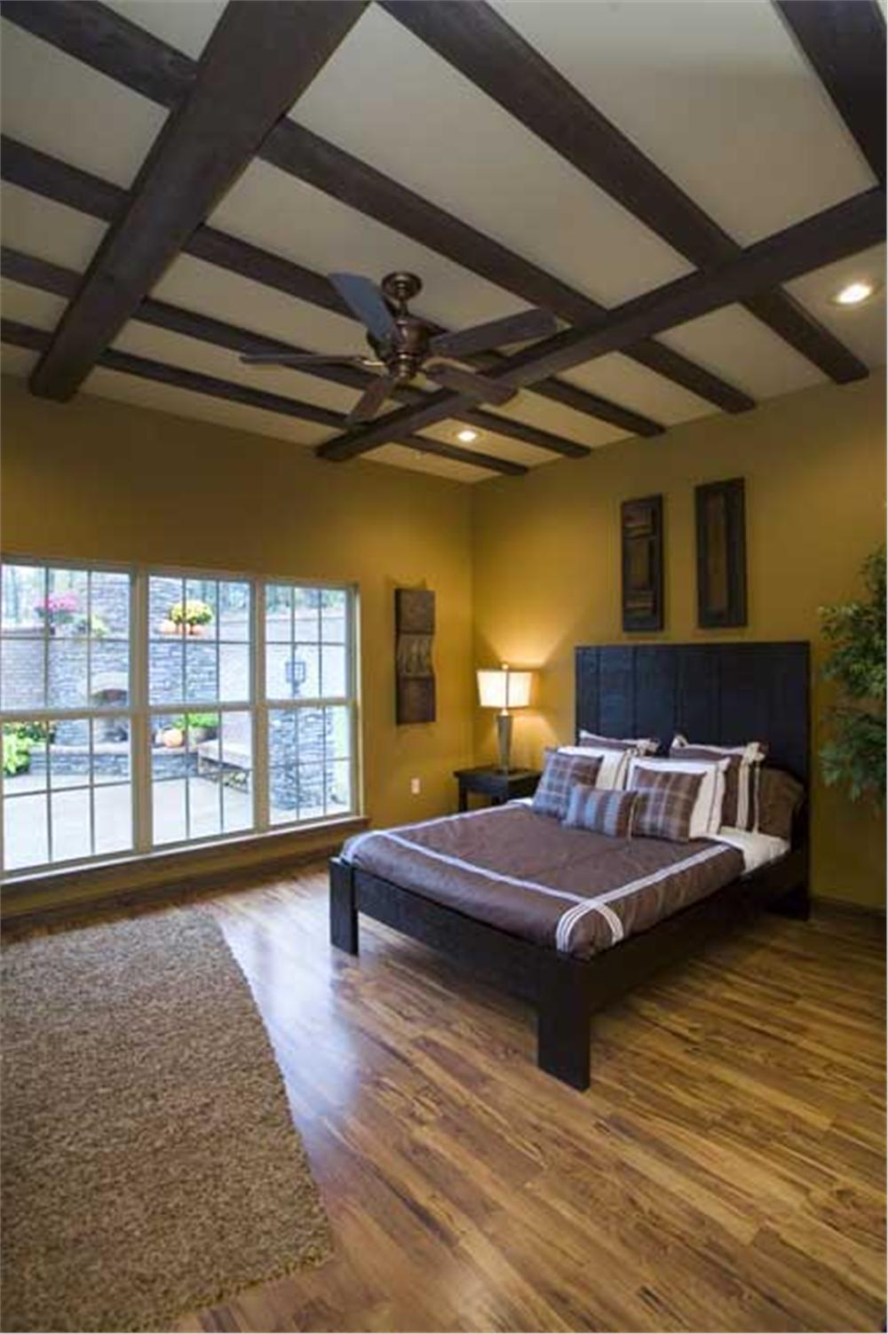 Master bedroom with wood floor and timber-accented ceiling