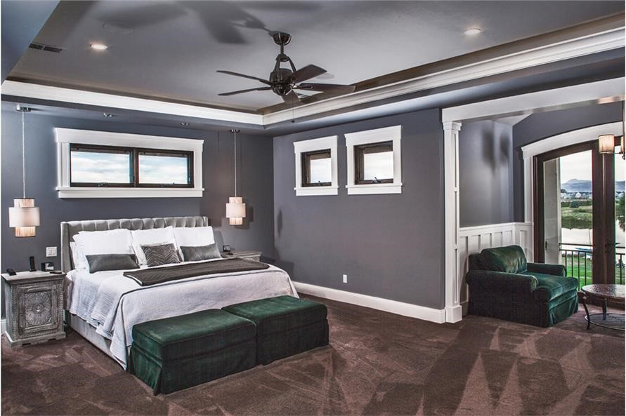 Large master bedroom suite with sitting room seen on the right with green easy chair