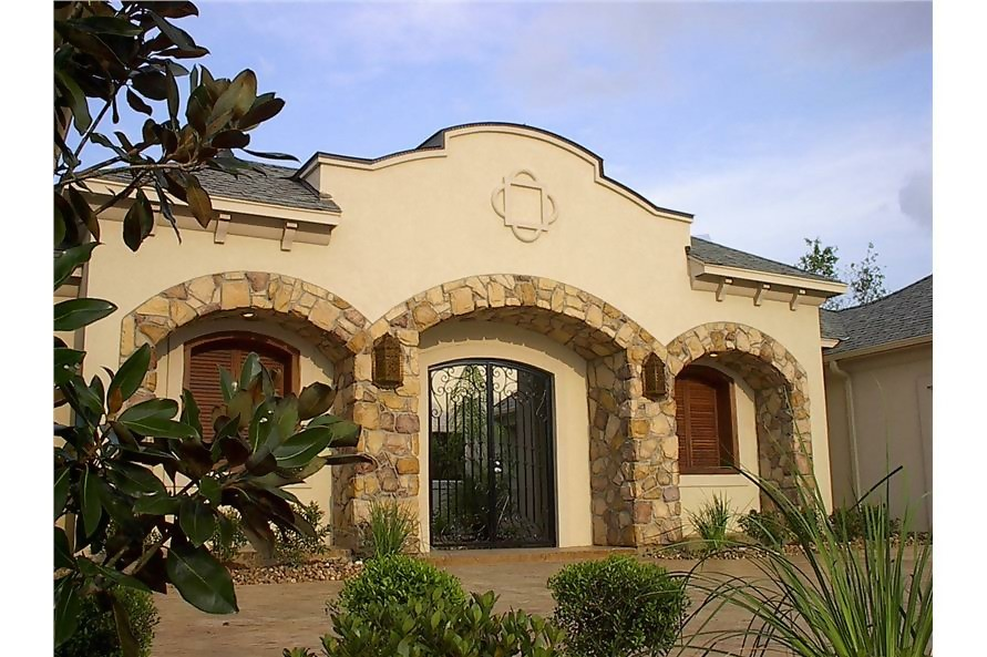 Spanish style home with beige stucco, curved windows, and quatrefoil in front facade