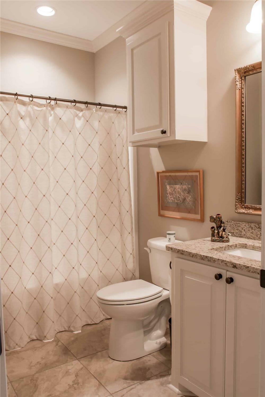 Water-saving toilet between the vanity and tub area in a bathroom