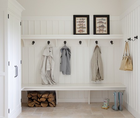 White paneled mudroom with bench, hooks for clothing, and overhead shelves