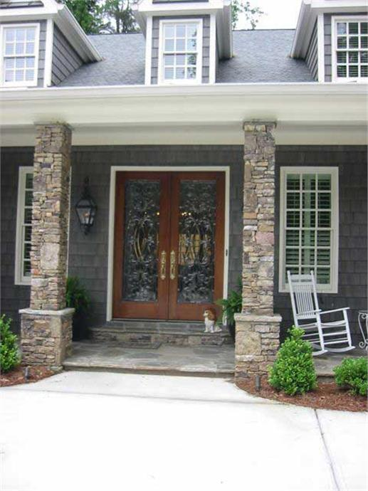 square stone columns on pedestals and the decorative glass panes on the front door