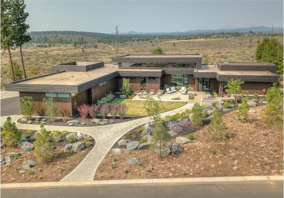 Modern style home with landscaped courtyard, patios, and covered front and rear porches