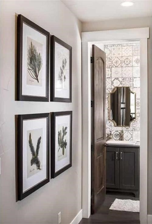 Powder room with geometric wallpaper and mirror with complementing shape