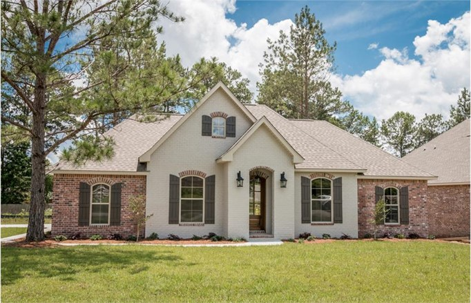 French style home with tall hip and gable rooflines, brick and stucco siding, and arched windows with shutters
